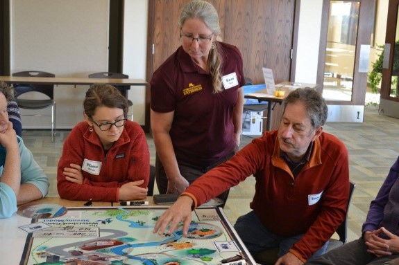 Maeve Maron of Morris, Karen Terry of U of M Extension and Stewart Day of Minnesota review possible outcomes in the Watershed Game.
