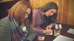 Two women writing postcards to their member of congress.