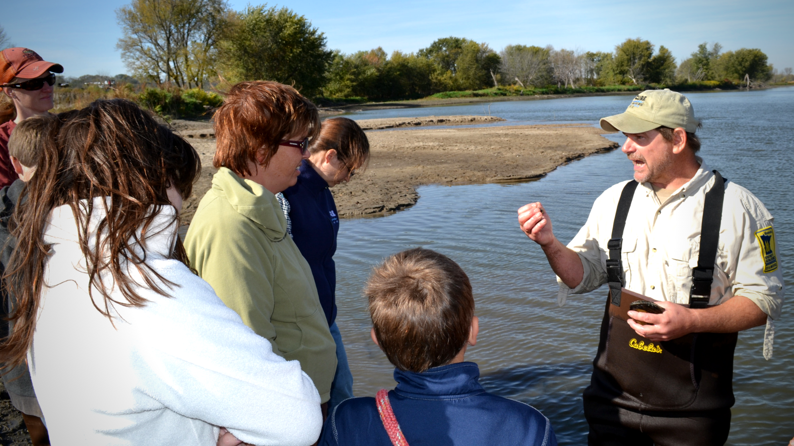 People learning about mussels in a river.