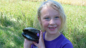 A girl holding a mussel