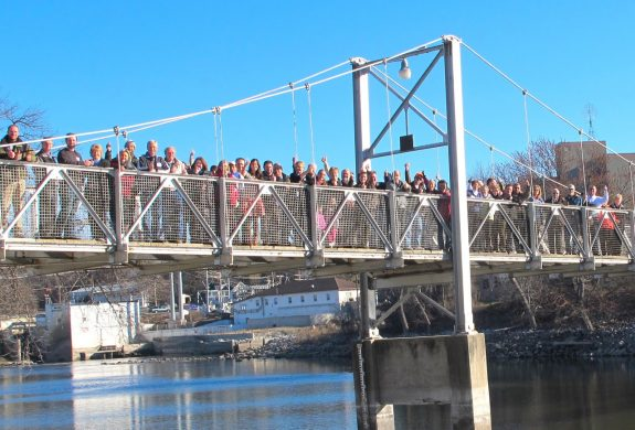 People gathered on the walking bridge across the Minnesota River in Granite Falls