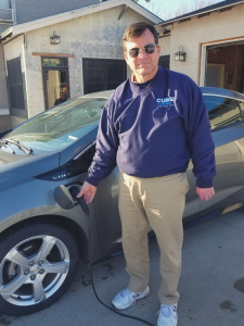 Pete plugging in his Chevy Volt by his Murdock home.