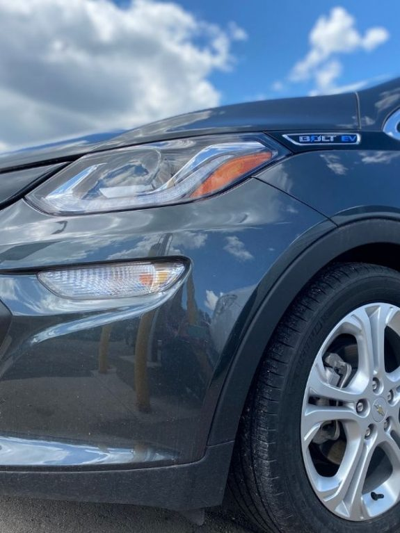 front of a Chevy Bolt + clouds