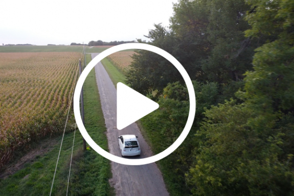Play icon over a car driving down a gravel driveway with fields and powerlines