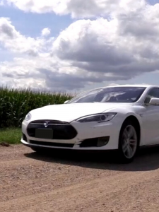 A Tesla Model S on a gravel road by a corn field