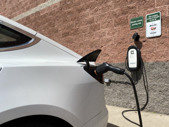 An electric vehicle plugged into a charger at a grocery store.